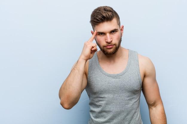 Młody przystojny sprawność fizyczna mężczyzna wskazuje świątynię z palcem, myśleć, skupiający się na zadaniu.