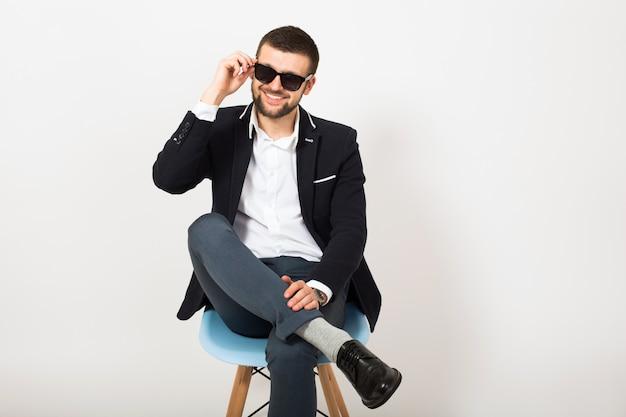 Młody przystojny stylowy hipster mężczyzna w czarnej kurtce, styl biznesowy, biała koszula, na białym tle, siedzi zrelaksowany na krześle biurowym, rozmawia na smartfonie, uśmiechnięty, szczęśliwy, pozytywny, okulary przeciwsłoneczne