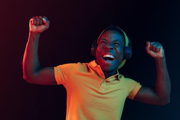 Młody przystojny szczęśliwy hipster mężczyzna słuchanie muzyki w słuchawkach w czarnym studio