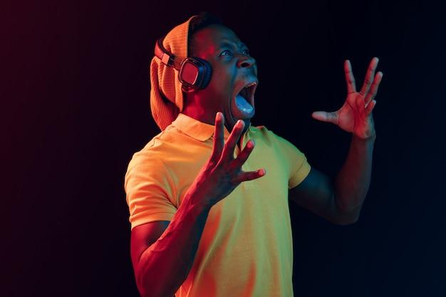 Młody przystojny szczęśliwy hipster mężczyzna słuchanie muzyki