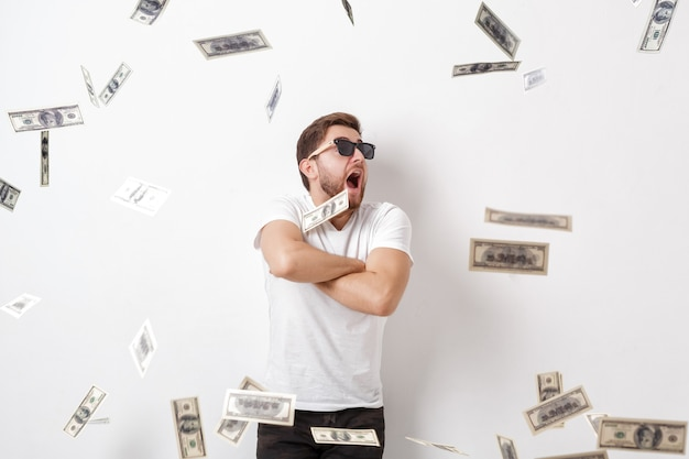 Młody przystojny szczęśliwy mężczyzna z brodą w białej koszuli stojący pod deszczem pieniędzy z banknotów dolarowych