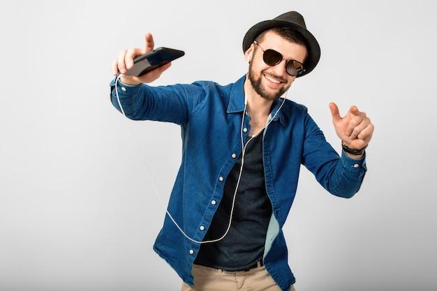 Młody przystojny szczęśliwy uśmiechnięty mężczyzna słuchający muzyki w słuchawkach na białym tle na tle białego studia, trzymając smartfon, na sobie dżinsową koszulę, kapelusz i okulary przeciwsłoneczne