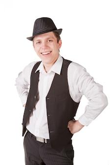 Młody przystojny szczęśliwy uśmiechnięty nowożytny mężczyzna jest ubranym kurtkę, białą koszula, czarnych spodnia i kapelusz pozuje w studiu odizolowywającym na bielu.