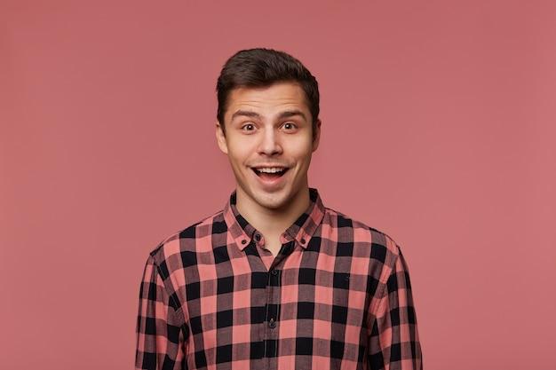Młody przystojny szczęśliwy zdumiony facet w kraciastej koszuli, patrzy w kamerę z zaskoczeniem, iso; ated na różowym tle z szeroko otwartymi ustami.