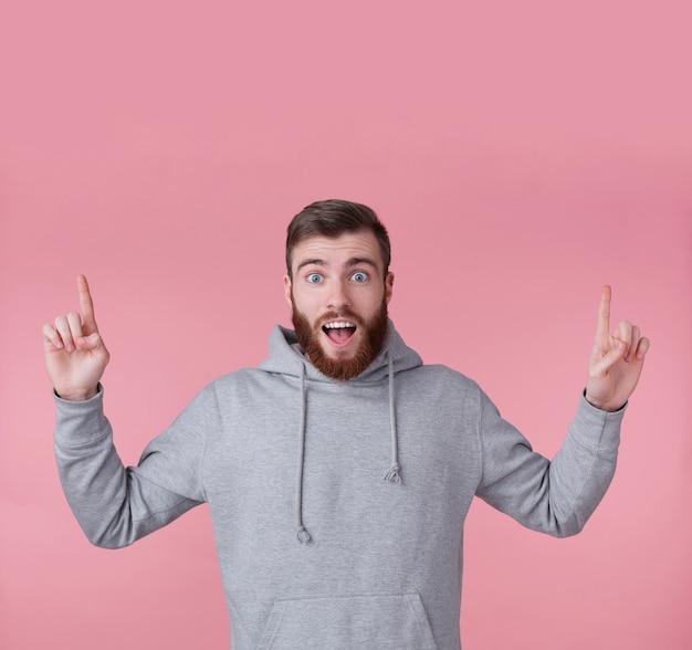 Młody przystojny szczęśliwy zdumiony rudy brodaty mężczyzna w szarej bluzie z kapturem, stoi na różowym tle, patrzy w kamerę z szeroko otwartymi ustami i oczami, chce zwrócić na siebie uwagę i wskazuje na skopiowanie miejsca.