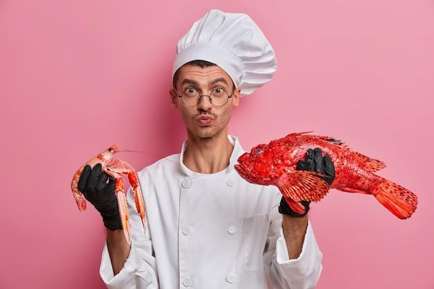 Młody przystojny szef kuchni trzymający surowe raki na białym tle
