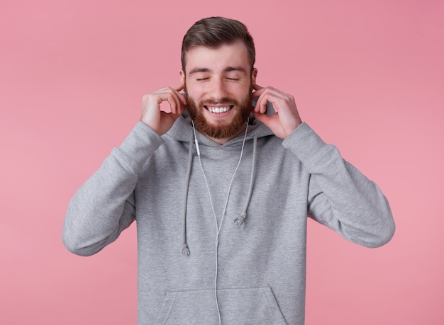 Młody przystojny, szeroko uśmiechnięty rudobrody mężczyzna w szarej bluzie z kapturem, wygląda na szczęśliwego i zadowolonego, słuchając swojej ulubionej piosenki w słuchawkach, stoi na różowym tle z zamkniętymi oczami.