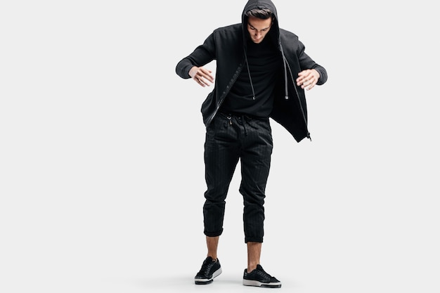 Młody przystojny tancerz ubrany w czarne spodnie i bluzę