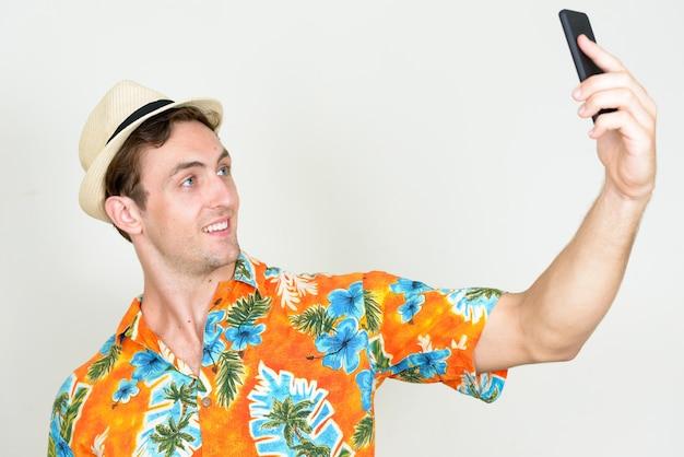 Młody przystojny turysta mężczyzna gotowy na wakacje na białym tle