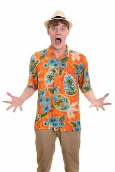 Młody przystojny turysta mężczyzna z kapeluszem wygląda zaskoczony, gotowy na wakacje