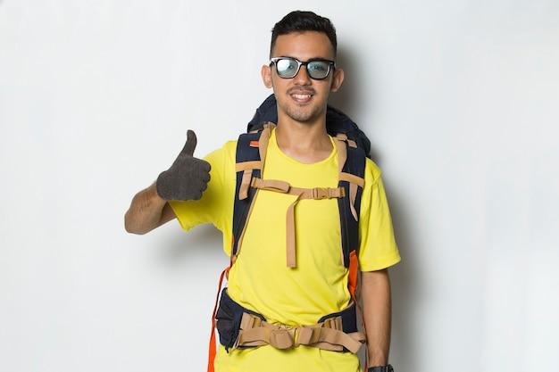 Młody Przystojny Turysta Mężczyzna Z Plecakiem Pokazując Kciuk Do Góry Ok Gest Na Białym Tle Premium Zdjęcia