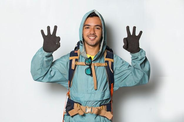 Młody przystojny turysta mężczyzna z plecakiem pokazując kciuk do góry ok gest na białym tle