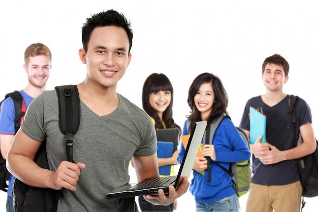 Młody przystojny uczeń z laptopem i przyjaciółmi przy tłem