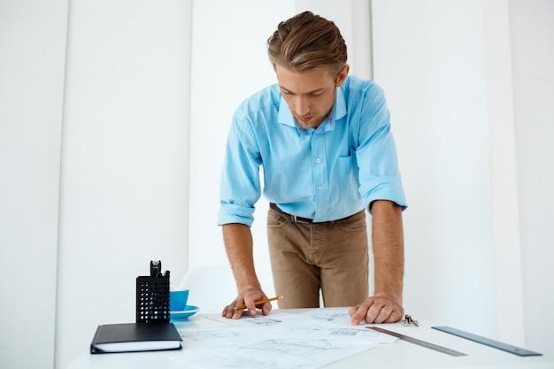 Młody przystojny ufny zadumany biznesmen pracująca pozycja przy stołowym rysunku nakreśleniem. . białe nowoczesne wnętrze biura