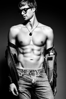 Młody przystojny umięśniony sprawny mężczyzna model mężczyzna pozowanie studio pokazując swoje mięśnie brzucha w skórzanej kurtce