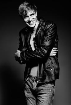 Młody przystojny umięśniony sprawny mężczyzna model mężczyzna w skórzanej kurtce pozowanie studio pokazano jego mięśnie brzucha