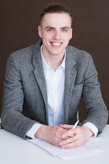 Młody przystojny uśmiechnięty biznesowy mężczyzna.