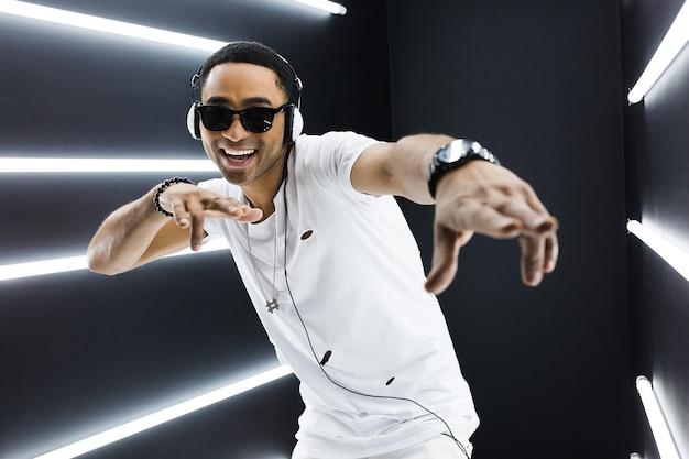 Młody przystojny uśmiechnięty hipster czarny człowiek w białym stroju słuchając muzyki na słuchawkach i tańcząc w stylu hip hop w nocnym klubie disco, bawiąc się