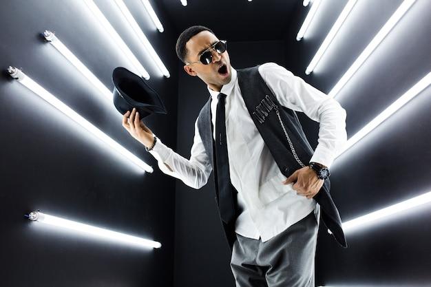 Młody przystojny uśmiechnięty hipster czarny człowiek w stylu retro vintage garnitur taniec hip hop w klubie nocnym disco, zabawy