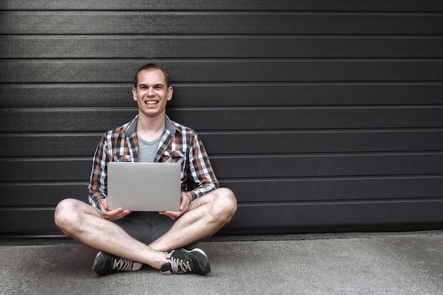 Młody przystojny uśmiechnięty mężczyzna siedzi przy ścianie z laptopem
