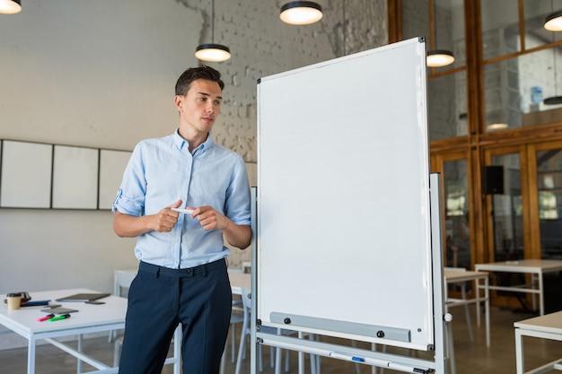 Młody przystojny uśmiechnięty mężczyzna stojący przy pustej białej tablicy z markerem