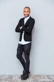 Młody przystojny uśmiechnięty mężczyzna stojący z rękami skrzyżowanymi na białym tle
