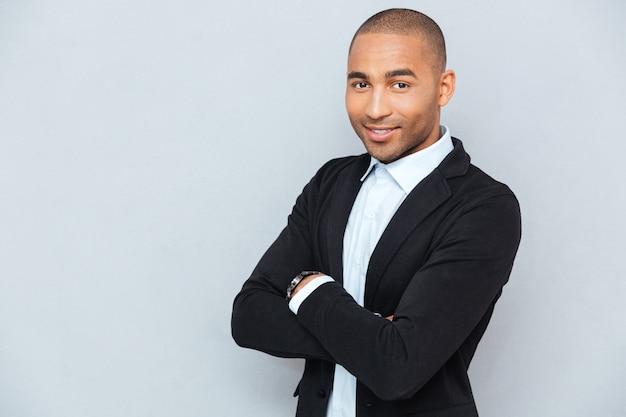 Młody przystojny uśmiechnięty mężczyzna stojący ze skrzyżowanymi rękami