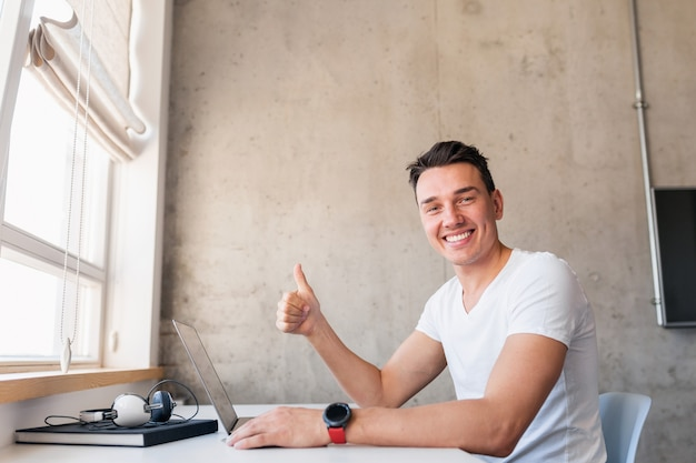 Młody przystojny uśmiechnięty mężczyzna w casual strój siedzi przy stole, pracując na laptopie, freelancer w domu