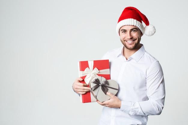 Młody przystojny uśmiechnięty mężczyzna z prezentami