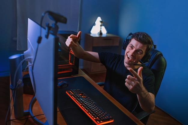 Młody przystojny vloger prowadzi transmisję na żywo podczas grania w gry wideo online w domu na pc
