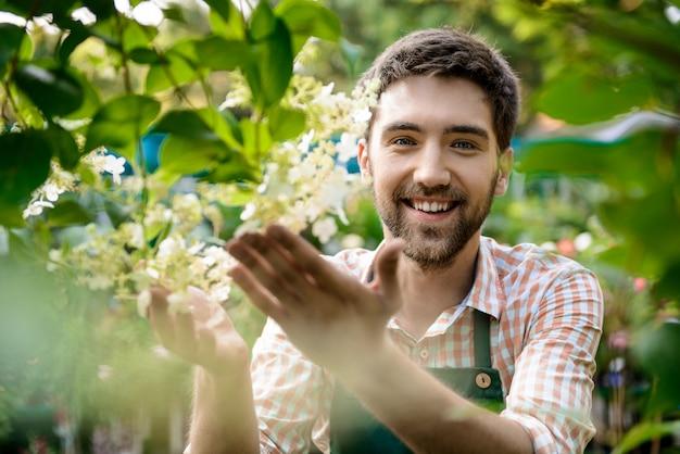 Młody przystojny wesoły ogrodnik uśmiechnięty, dbanie o kwiaty