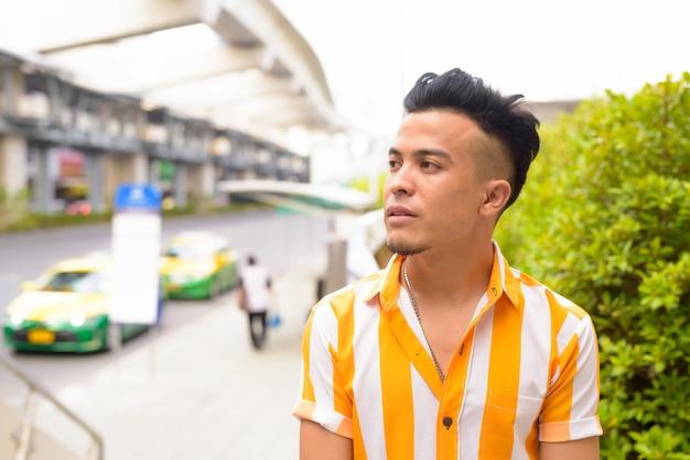 Młody przystojny wielu etnicznych człowiek myśli na ulicach miasta