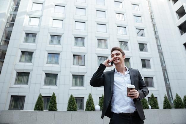 Młody przystojny zajęty mężczyzna rozmawia przez telefon w centrum biznesu