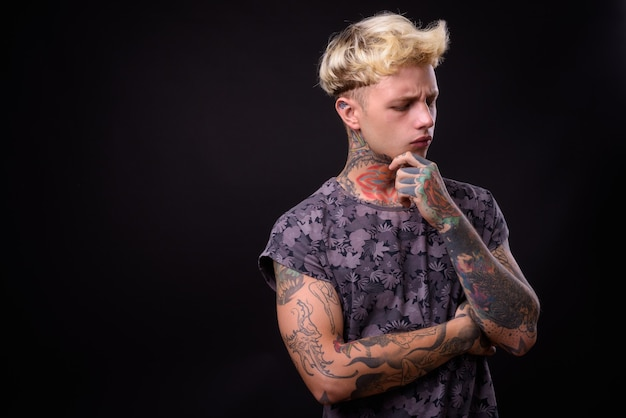 Młody przystojny zbuntowany mężczyzna z blond włosami i tatuażami