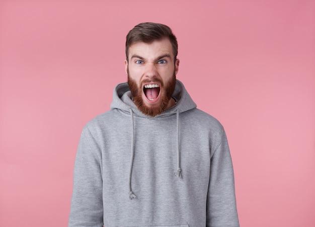 Młody przystojny zły, rudy brodaty mężczyzna w szarej bluzie z kapturem, wygląda agresywnie i zszokowany, stoi na różowym tle i krzyczy.