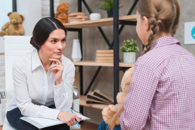 Młody psycholog obserwuje małej dziewczynki obsiadanie przed ona
