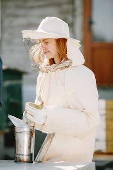 Młody pszczelarz uczy się od swojego nauczyciela. ciekawa kobieta w kombinezonie.