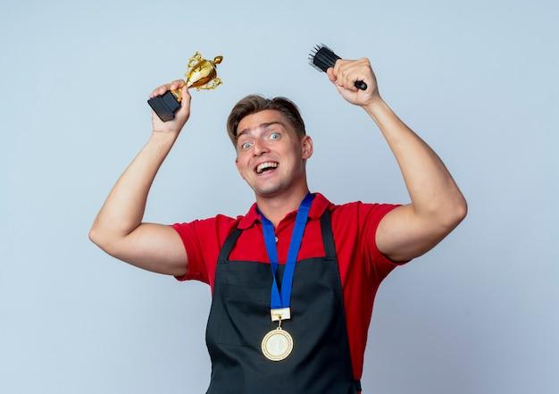 Młody radosny blond męski fryzjer w mundurze ze złotym medalem trzyma puchar zwycięzcy i grzebień na białym tle na białej przestrzeni z miejsca na kopię