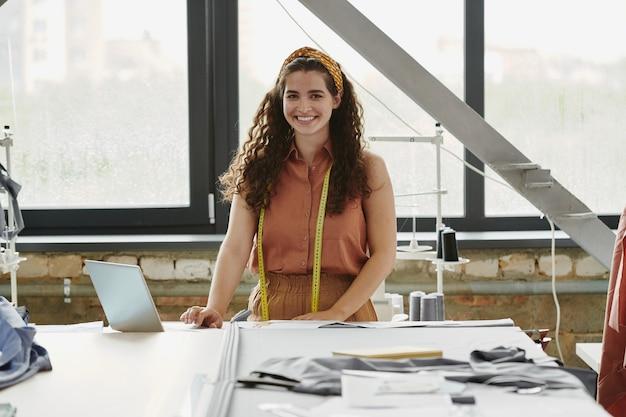 Młody radosny, kreatywny projektant ubrań patrzy na ciebie, czekając na nowych klientów i pracujący nad kolekcją mody w miejscu pracy