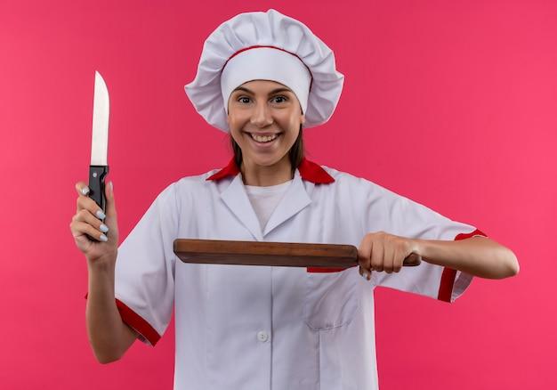 Młody radosny kucharz kaukaski dziewczyna w mundurze szefa kuchni trzyma nóż i deskę do krojenia na różowej przestrzeni z miejsca na kopię