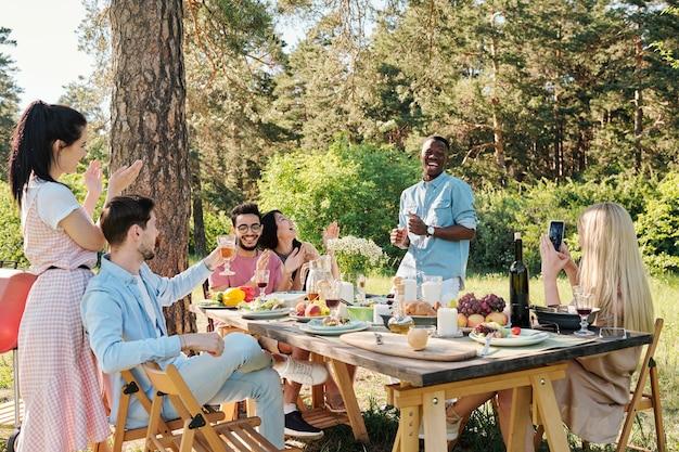 Młody radosny mężczyzna pochodzenia afrykańskiego tańczy przy świątecznym stole przed przyjaciółmi po kolacji na świeżym powietrzu, podczas gdy jedna z dziewcząt nagrywa wideo