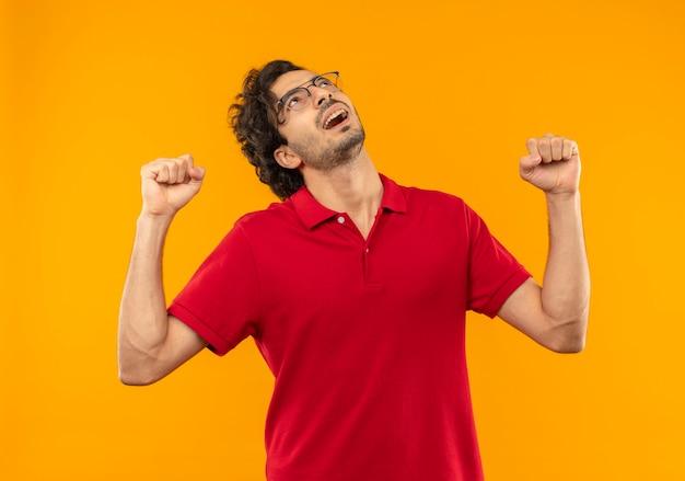 Młody radosny mężczyzna w czerwonej koszuli z okularami optycznymi podnosi pięści i patrzy w górę na białym tle na pomarańczowej ścianie