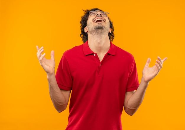 Młody radosny mężczyzna w czerwonej koszuli z okularami optycznymi podnosi ręce i patrzy w górę na białym tle na pomarańczowej ścianie