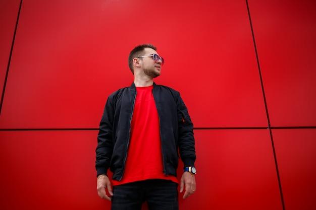 Młody radosny mężczyzna z brodą z pozytywnym uśmiechem w koszulce w modnej czarnej kurtce w koszulce pozuje w pobliżu czerwonego metalowego budynku w mieście. szczęśliwy facet miejski na ulicy. męska odzież