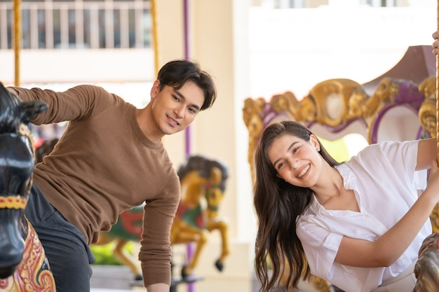 Młody radosny para mężczyzna i kobieta na koniu w parku rozrywki carousel