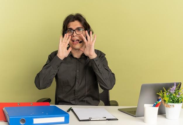 Młody radosny pracownik biurowy mężczyzna na słuchawkach w okularach optycznych siedzi przy biurku z narzędziami biurowymi za pomocą laptopa udaje, że dzwoni do kogoś izolowanego na zielonym tle z przestrzenią do kopiowania