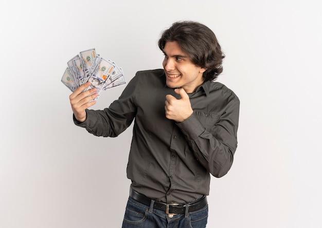 Młody radosny przystojny kaukaski mężczyzna trzyma i patrzy na pieniądze na białym tle na białym tle z miejsca na kopię