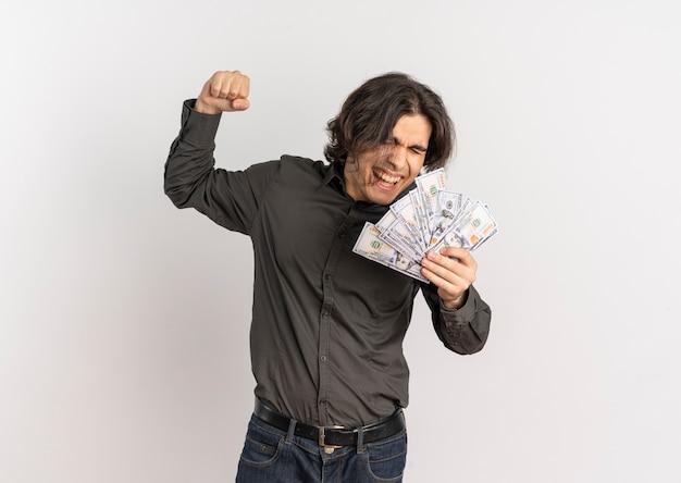 Młody radosny przystojny kaukaski mężczyzna trzyma pieniądze i podnosi pięść