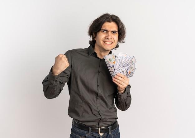 Młody radosny przystojny kaukaski mężczyzna trzyma pieniądze i trzyma pięść na białym tle na białym tle z miejsca na kopię