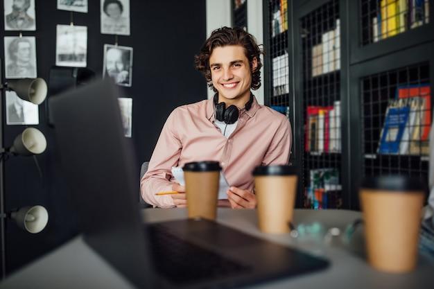 Młody radosny student siedzący w bibliotece uniwersyteckiej podczas przerwy na kawę od nauki